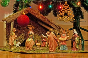 christmas nativity scene with hand-colored ceramic figures and below tree with many decorations (lights, bauble and star)